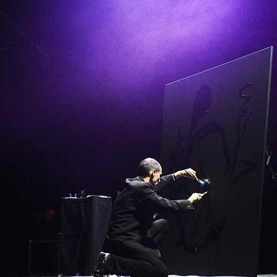 Peintre performer en pleine action pour la réalisation d'un portrait colle et paillettes - France