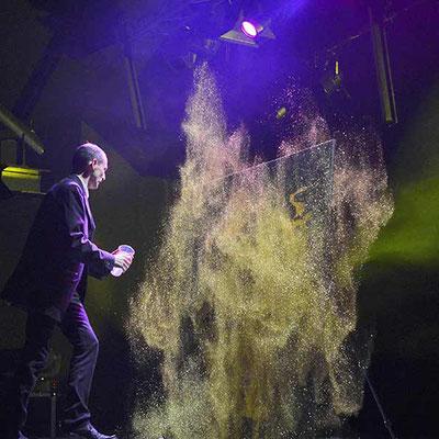 Le peintre performer EriK BLACK jetant des paillettes sur une toile pour révéler un portrait de star - final du spectacle