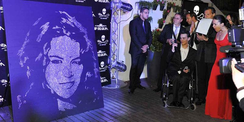 L'actrice américaine Michelle Rodriguez découvre son portrait paillettes réalisé à l'instant - Festival de Cannes 2012