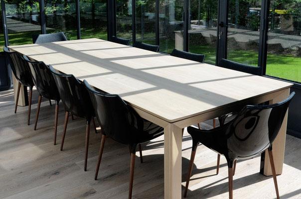 table en chêne blanchi + verni mat. plateau de 3m30 de long avec chants en aile d'avion associés aux coupes d'onglet des piétements, chaises Starck
