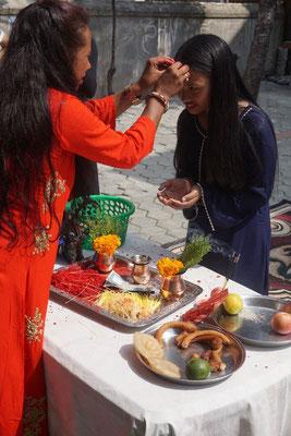 Neben der Segnung erhält jeder auch etwas Obst, Geld und Gebäck (z.B. SelRoti ein in fett ausgebackener Kringel der meistens speziell zu Dashain und Tihar gebacken wird.)