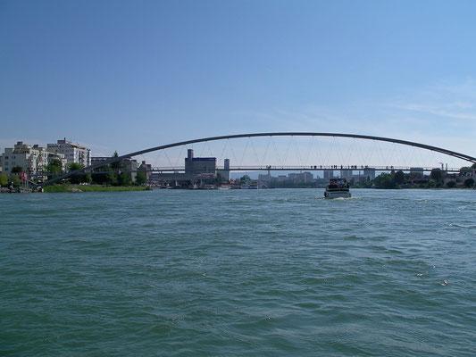 """Die """"Passerelle des Trois Pays"""" führt von Frankreich nach Deutschland. Sie berührt die Schweiz nicht. Blick von der Mitte des Rheins südwärts zur Passerelle. Dahinter die Stadt Basel."""