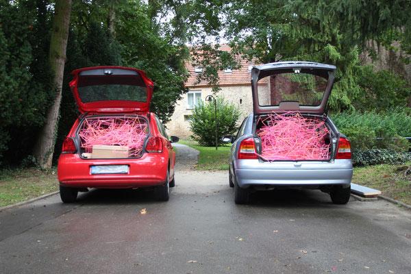 2 Kleinwagen bis an den Rand gefüllt mit Neontrinkhalme- Clustern