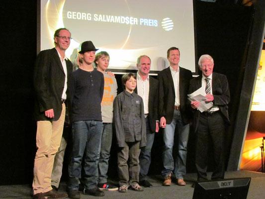 Stolze Gewinner auf einer Bühne mit Franz Alt