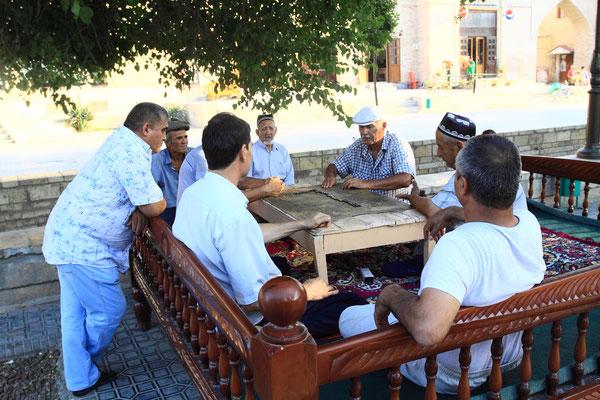 Nach dem Gebet vergnügen sich die Männer im Schatten eines Maulbeerbaumes beim Dominospiel.