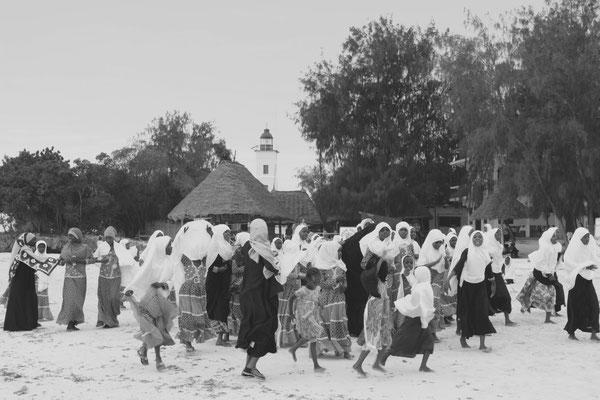 Nach der Schule spielen und singen die Mädchen unbeschwert am Strand.