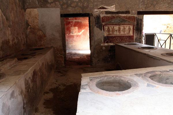 Im Thermopolium wurden Getränke und warme Speisen serviert, die in großen Krügen aufbewahrt wurden. Diese waren in die reich verzierten gemauerten Tresen eingelassen.