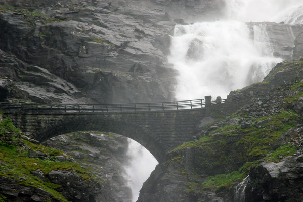 Über die Sogge-Brücke mit nur einer Fahrspur und ständiger Gischt durch die Wasserfälle von Stigfoss. Der Sage nach ist dort ein Troll ums Leben gekommen, weil er einem schönen Mädchen beim Baden zuschaute und dabei den Sonnenaufgang übersah