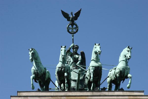 die geflügelte Siegesgöttin Viktoria dar, die einen von vier Pferden gezogenen Wagen (Quadriga) in die Stadt hineinlenkt. Sie blickt nach Osten in Richtung Stadtschloß