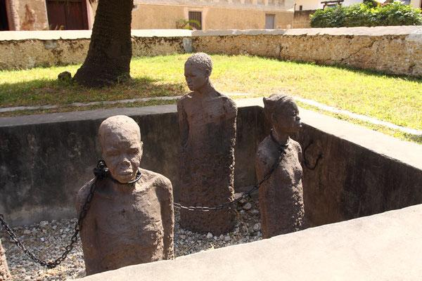 Ein Mahnmal erinnert an den unmenschlichen Ort, an dem Kaufinterressierte mit grausamen Hieben am Prügelstock die Widerstandsfähigkeit ihrer zukünftigen Sklaven überprüften.
