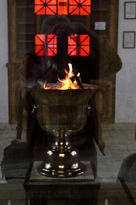 Von der Eingangshalle aus blickt man durch eine Glasscheibe auf den Altar mit dem ewigen Feuer, das anfänglich anderenorts durchgängig seit 460 v. Chr. brennt.