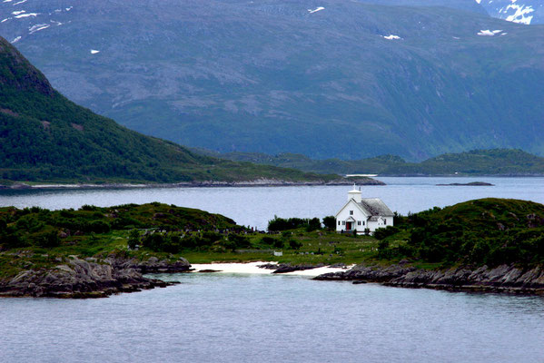 Ausfahrt des Schiffes Richtung Lofoten vorbei an einer kleinen Insel mit Kirche und Friedhof