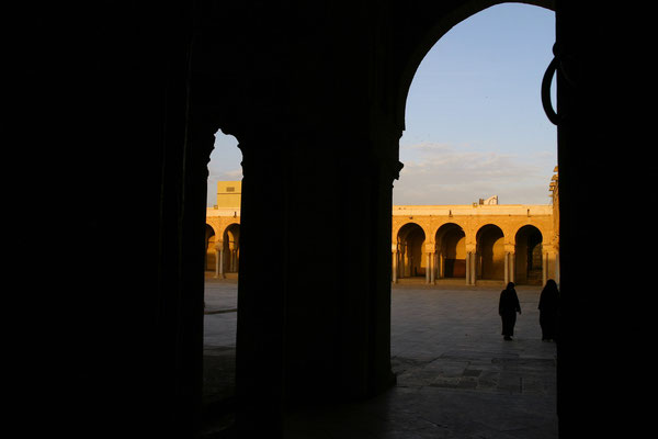 """Im Volksmund kurz """"Sīdī ʿOqba"""", heute noch das Wahrzeichen der Stadt, ist sie bereits gegen 670 vom Eroberer Nordafrikas Uqba ibn Nāfi neben dem Lagerplatz des muslimischen Heeres in ihren Ursprüngen gegründet worden."""