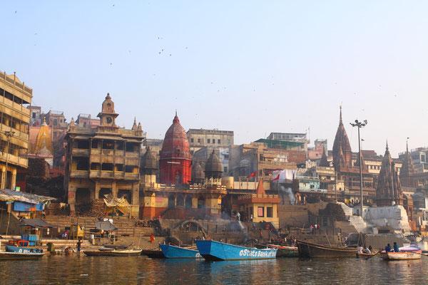 Im Hintergrund ein Hospiz für die Todgeweihten. Wer hier stirbt, so heißt es, entkommt dem Rad der Wiedergeburten. So reisen viele Hindus aus ganz Indien am Ende ihres Lebens hier her nach Varanasi. Hier wollen sie sterben.
