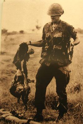 wie eine Trophäe halt der Soldat die zerfetzte Leiche eines Vietnamesen hoch
