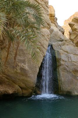 Vom zerstörten Dorf führt ein Weg in die Oase mit einem kleinen Wasserfall. Denn das Überleben dieser Oasen war nur durch ein unterirdisches Wasserleitungssytem möglich, das die Vorräte im Berg anzapft und über Kanäle weiterleitet.