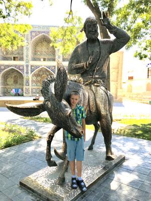 Hodscha Nasreddin, der orientalische Till Eulenspiegel, sitzt auf seinem Esel und schaut sich das Treiben an.