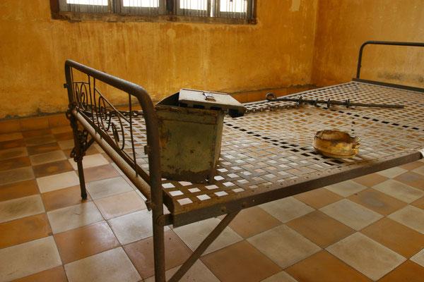 Die Aufnahme zeigt einen Blick in ein ehemaliges Klassenzimmer des jetzigen Zellblockes 4, in welchem die Gefangenen zu Dutzenden an Ketten gefesselt auf Ihren qualvollen Tod warteten.