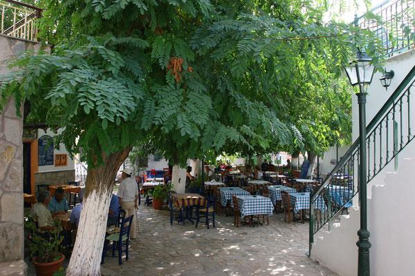 Rast in alter Taverne unter schattigen Bäumen