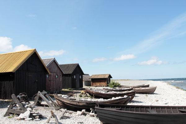 Fischerbuden aus Holz oder gestapelten Steinen mit Bretter- oder Schindeldächern stehen dicht beieinander, die Buden sehen altertümlich aus
