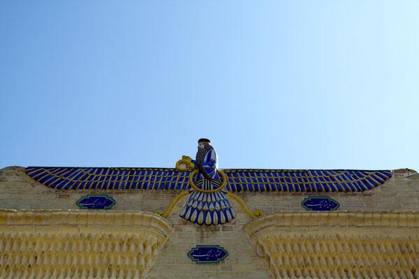 Über dem Säulenportal der Eingangsfassade schwebt das aus glasierten Fliesen hergestellte Symbol des Gottes Ahura Mazda.