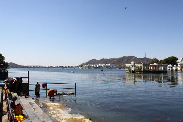 """Bekannt geworden durch den James Bond Film """"Octopussy"""" ist das auf dem Lake Pichola schwimmende """"Lake Palace Hotel"""".  Die Fassade mit den weissen Palästen genießt man am besten von der gegenüberliegenden Halbinsel."""
