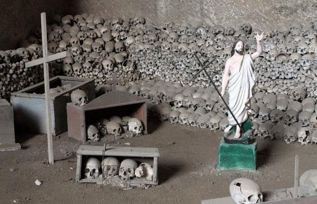Man sieht massenhaft Skelette und Schädel sowie Kreuze und andere sakrale Objekte, die auf eine Kultstätte hindeuten