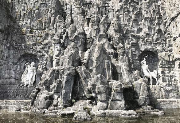 Die Szene wird von zwei weiteren mythologischen Figuren flankiert, die auf ihren durch Wasserdruck angetriebenen Hörnern blasen.