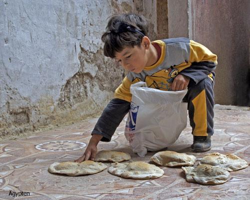 Das Kind zählt seine Brote aus der Armenspeisung in Alexandria (Ägypten)