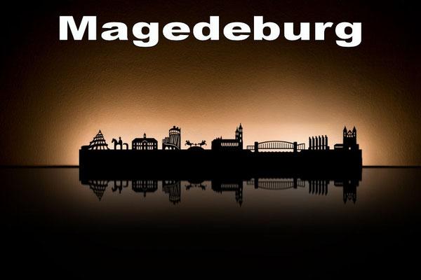 Objekte der Skyline (v.l.n.r.):  Jahrtausendturm, Stadtlogo, Rathaus, Hundertwasserhaus, Magdeburger Halbkugeln, Dom, Hubbrücke, Pferdetor, Kloster unserer lieben Frauen