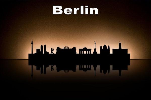 Objekte der Skyline (v.l.n.r.):  Fernsehturm, Potsdamer Platz, Berliner Bär, Reichstag, Brandenburger Tor, Siegessäule, Dom, Rathaus
