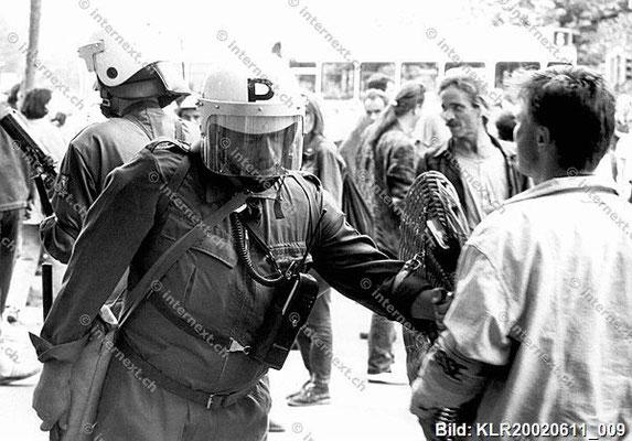 Stadtpolizei Zürich: Presse unerwünscht! Der Pressefotograf trägt eine Pressearmbinde. Im Schild des Polizisten ist eine Kamera eingebaut. 11/06/1992.;