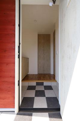 赤い外壁と白い扉、チェッカー柄の床がかわいい玄関