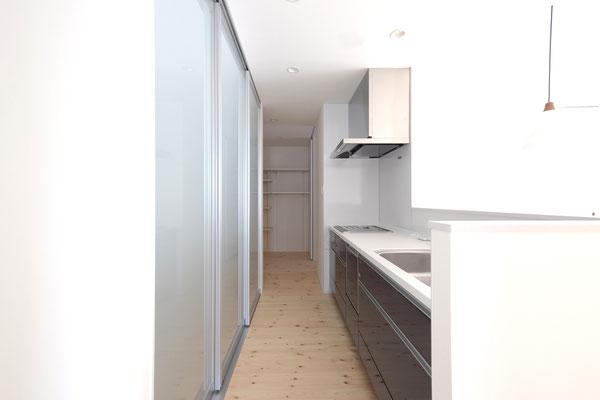 スタイリッシュな壁面収納を備え付けたシンプルなキッチン