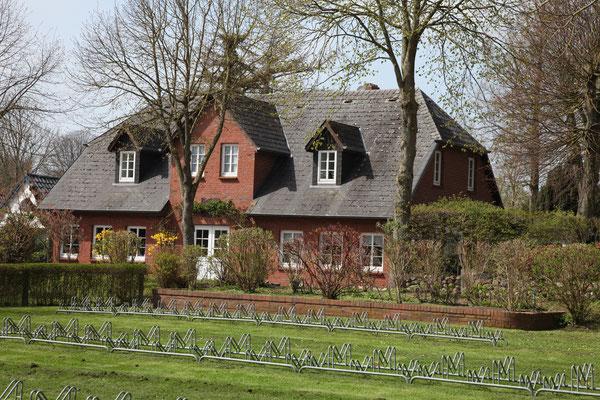 Blick vom roten Haus auf die Fahrradständer und das Haus Passat