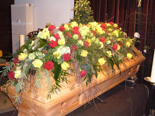 Sargbukett mit gelben und roten Rosen