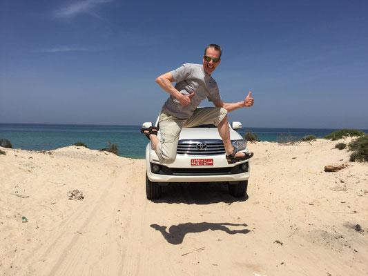 Auto-Jump an einem einsamen Strand in Oman, 2016