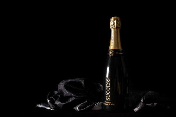 Champagne sur fond noir et foulard noir, mise en avant de la marque