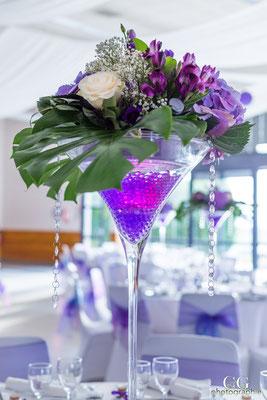Des compositions réalisées en vases martini. Hauteur 70 cm.