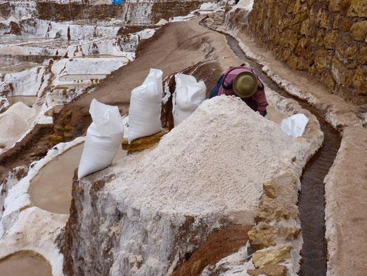Eine Alte Frau verpackt das gewonnene Salz in Säcke