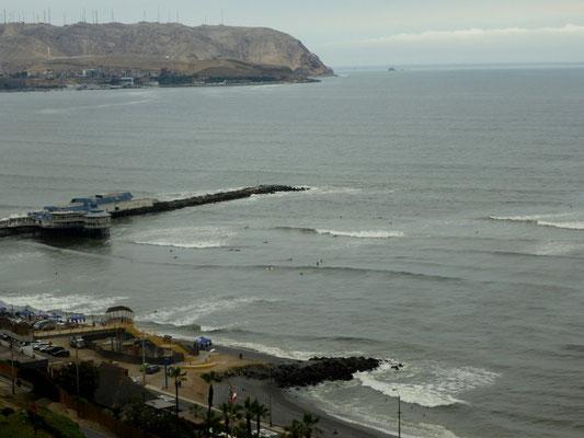 Neben dem Pier tummeln sich unzählige Surfer