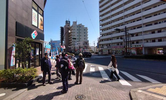 歩いてきた道(道路向こうのビルとビルの間)を振り返り、今立っている道とは元々一本の道だったという説明。