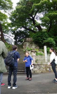 ・六代御前之墓の前で説明を聴く高校生  田越川の水の被害を受けないよう、階段を上がった右上柵の中に六代御前之墓があります。
