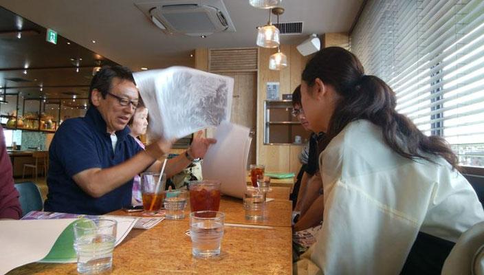 鎌倉駅に集合。鎌倉駅ビル2階のカフェで、団長から資料(A3-24枚)の説明と本日の行程の説明を受ける高校生。
