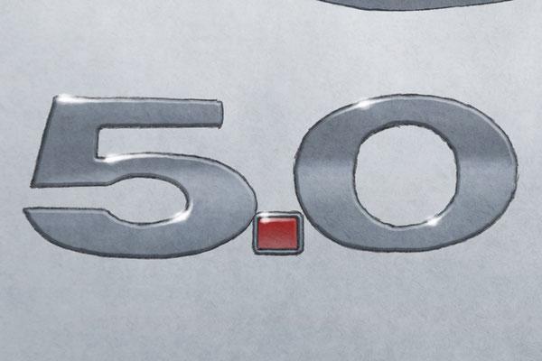L'emblème 5.0 apparait au bas à gauche du texte descriptif de la voiture