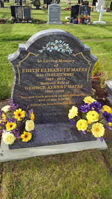 Photo of cleaned head stone and silk and fresh flower arrangements added