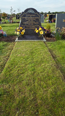 Grave site after full cleaning, grass cutting and fresh and silk flower arrangements added