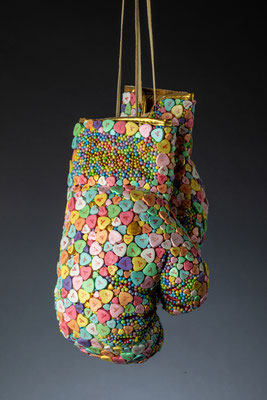 """Fuck It, 2020 19"""" x 14"""" x 6""""  boxing gloves, hand-made clay conversation hearts, foam beads, acrylic"""