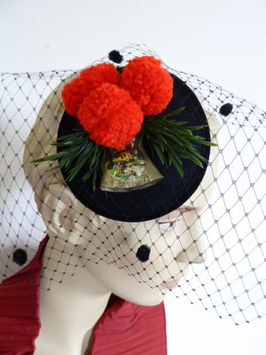 Black sinamay base with red pompoms and a vintage cow bell €59
