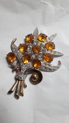 Silvertone pot metal, vestiges of vermeil on the stems and curlicue on front. Large orange rhinestones, complemented by clear RS - all in good condition. Rollover clasp. Forties. € 65